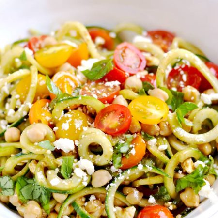 This spiralizer Greek salad is a light and refreshing side dish made with cucumbers, tomatoes, basil, chickpeas, feta cheese and balsamic vinaigrette. So easy and delicious! | APinchOfHealthy.com