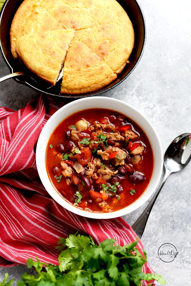 Healthy turkey chili in white bowl with cornbread and red towel