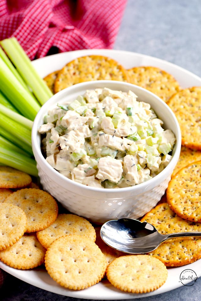 Chicken salad in a white bowl with crackers and celery