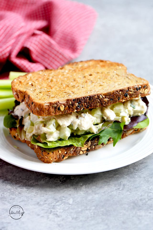 Chicken salad sandwich on a white plate with lettuce