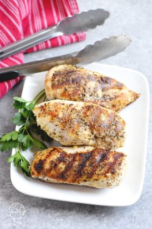 Grilled chicken breasts on a white plate with tongs and parsley
