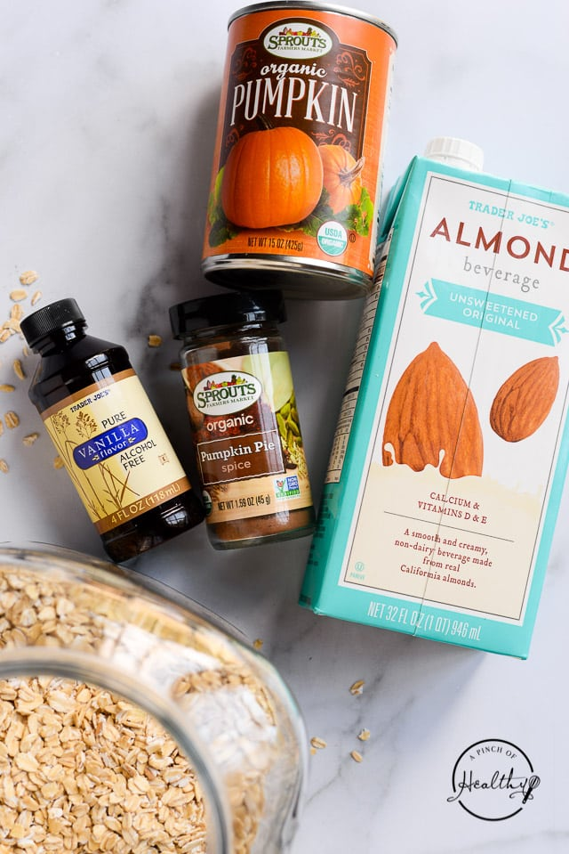 vanilla, pumpkin spice, almond milk, canned pumpkin and oats on marble counter