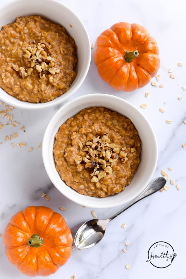 pumpkin spice oatmeal in two white bowls shot from overhead