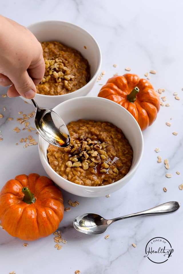 spoon drizzling maple syrup on pumpkin oatmeal