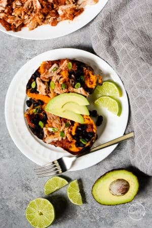 sweet potato with chicken, black beans, avocado and green onion on white plate with a fork