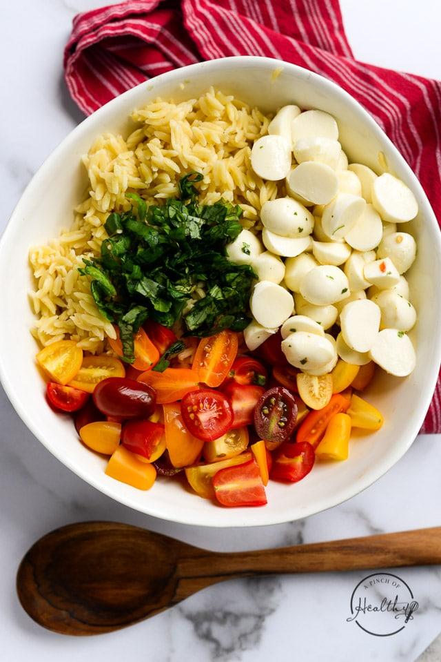 orzo pasta, basil, fresh mozzarella, rainbow tomatoes in a white bowl