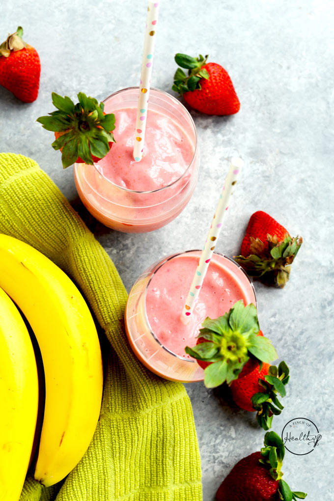 strawberry banana smoothies from overhead with fresh bananas and strawberries on gray surface
