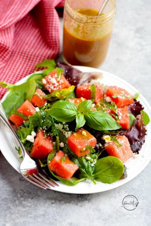 Watermelon feta salad with basil and balsamic vinaigrette on a white plate