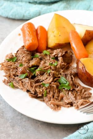 Classic pot roast with carrots and potatoes on a white plate closeup