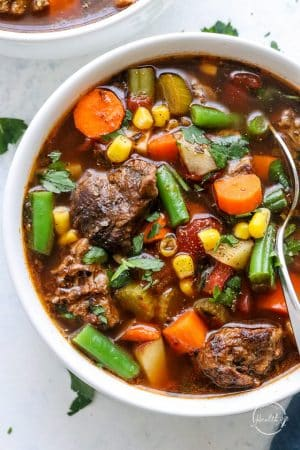 Closeup of vegetable beef soup in white bowl with spoon
