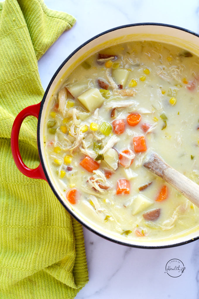 chicken corn chowder in red pot with green towel