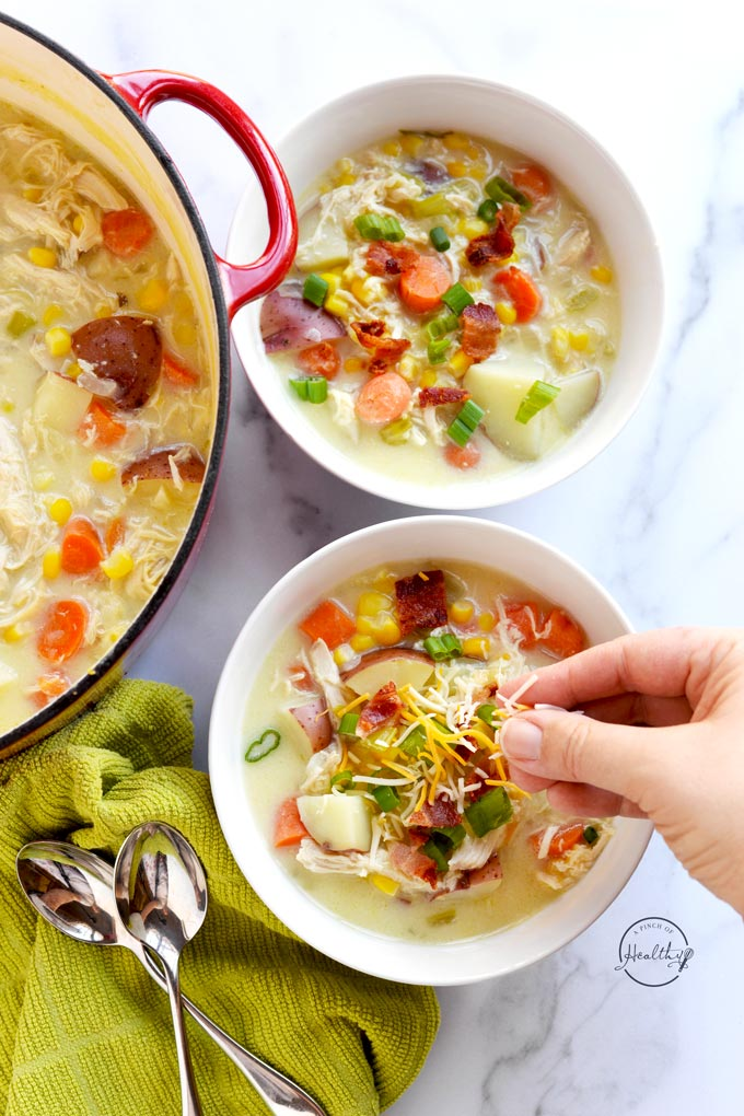 hand sprinkling cheese on a bowl of chicken corn chowder