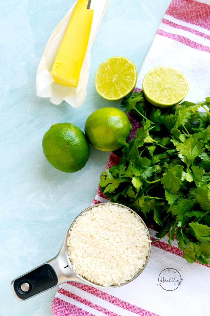 rice in a measuring cup with cilantro limes and butter on a blue background