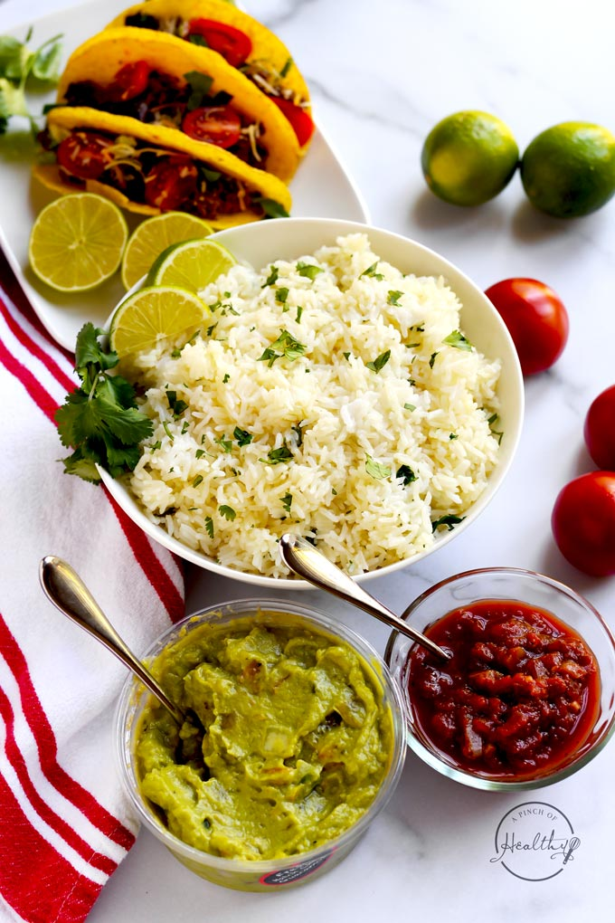 Tex Mex table scene with rice, tomato, lime, beef tacos, salsa and guacamole