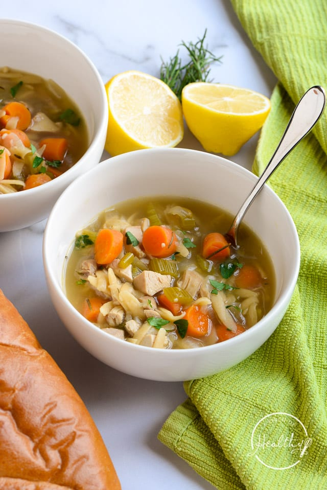 lemon chicken orzo soup in a white bowl with a spoon