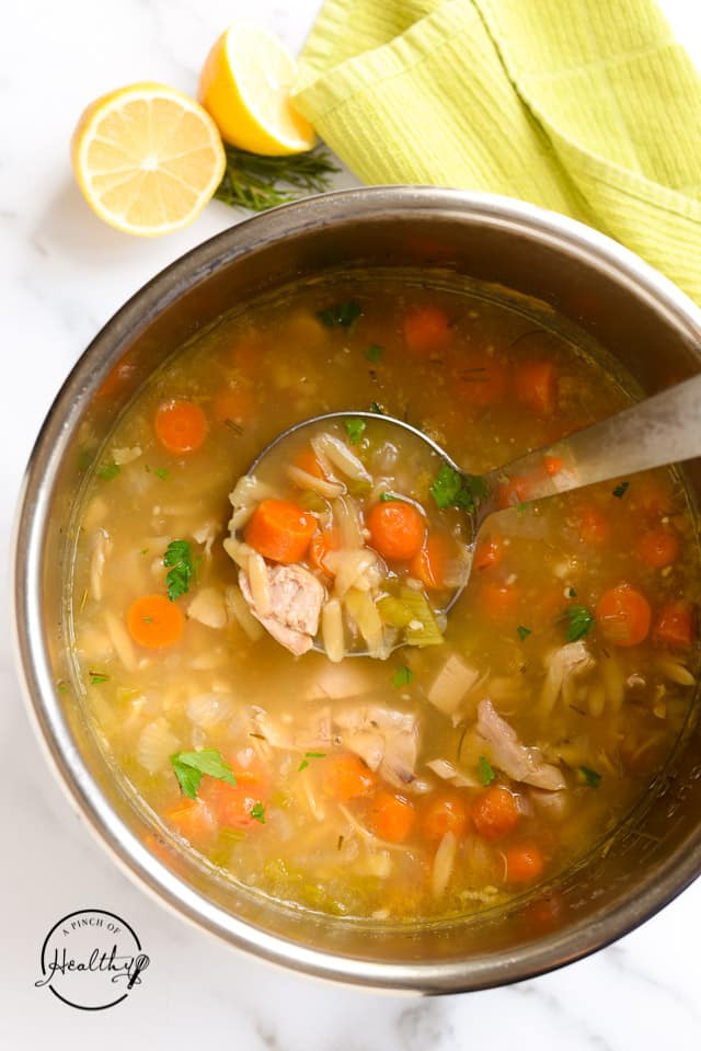 ladle dipping out chicken orzo soup from an Instant Pot