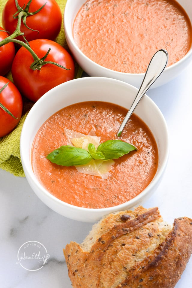 closeup of tomato basil soup in white bowl with shaved parmesan and fresh basil garnish