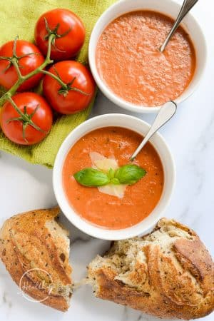 tomato basil soup in white bowls from overhead with crusty bread on marble counter
