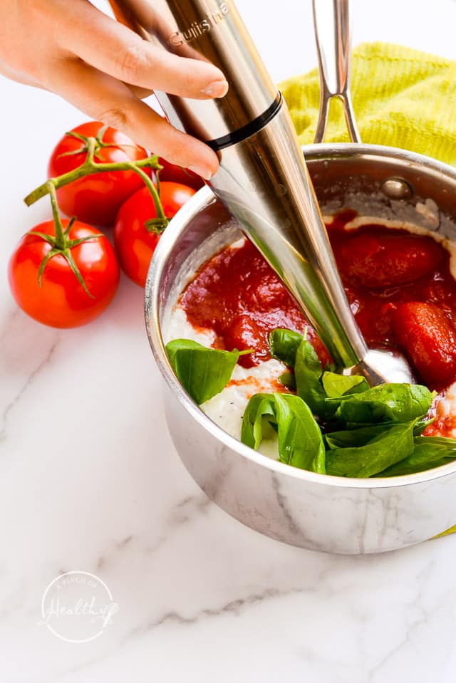 using immersion blender to puree tomatoes and basil into soup