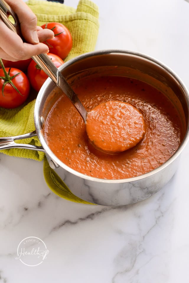 ladeling tomato basil soup out of a pot