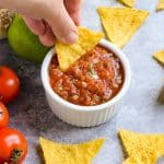hand dipping tortilla chip in salsa