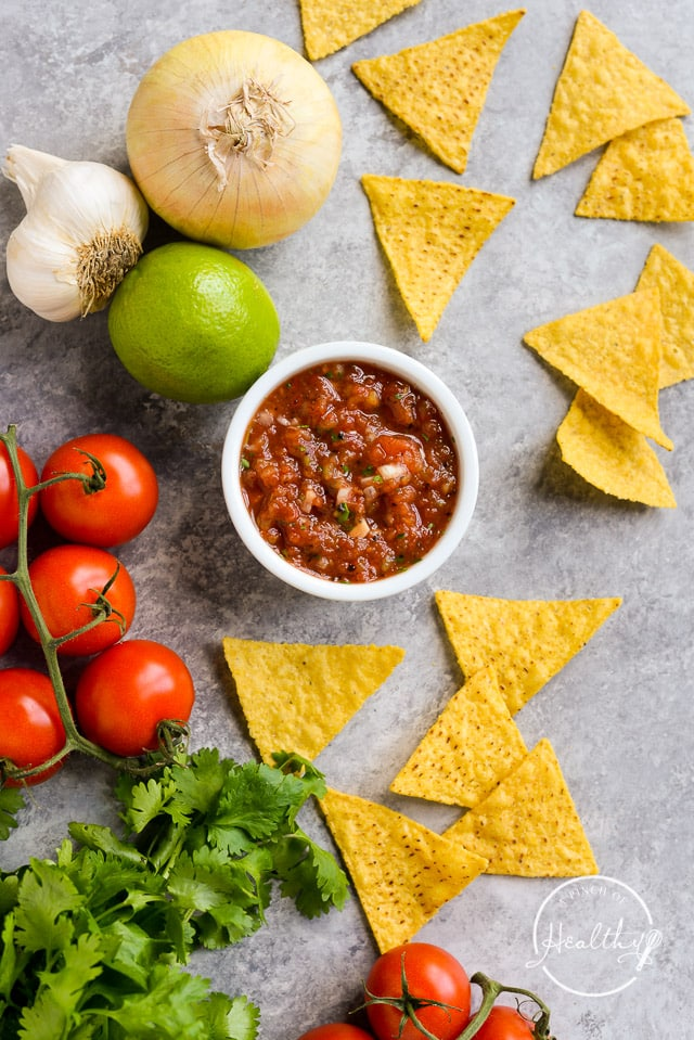 easy homemade salsa in a white bowl on gray counter with tortilla chips, tomatoes, lime, cilantro and garlic