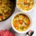 Chicken noodle soup in 2 white bowls overhead on marble counter with red towel