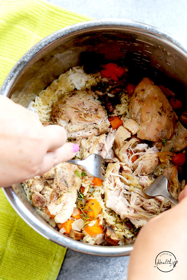 Instant Pot chicken and rice cooked in one pot two hands shredding chicken with forks