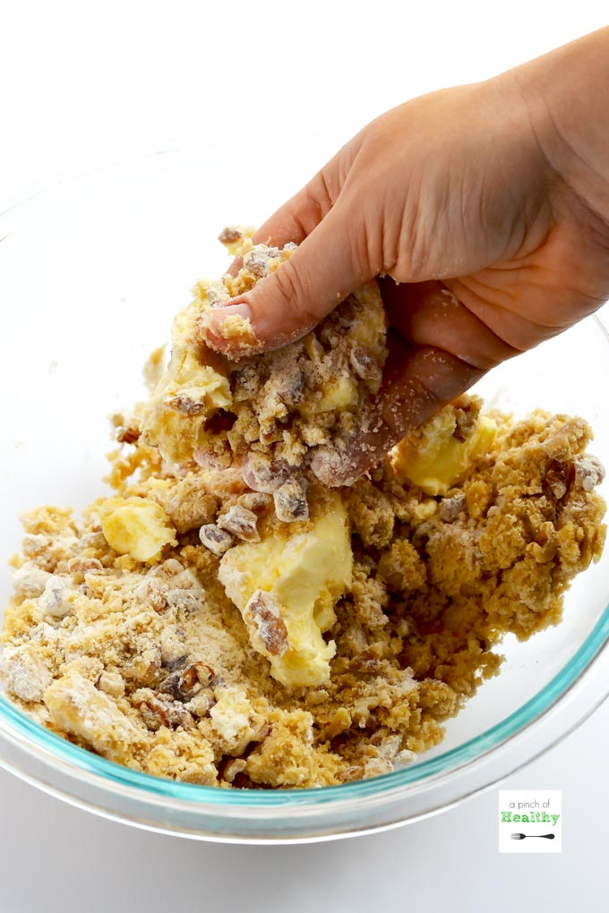Hand mixing butter, brown sugar and walnuts in clear mixing bowl