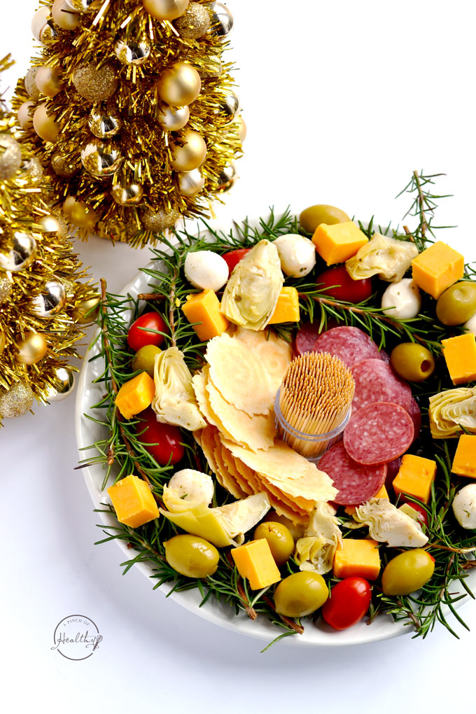 This antipasto Christmas wreath is the perfect easy appetizer for any holiday party, and you don't even have to cook anything. Just pick your favorite meats, cheeses and/ or veggies and assemble. | APinchOfHealthy.com