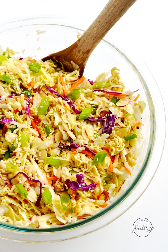 Asian slaw in clear bowl with wooden spoon