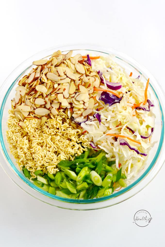 cabbage, almonds, green onion and ramen noodles in a clear bowl