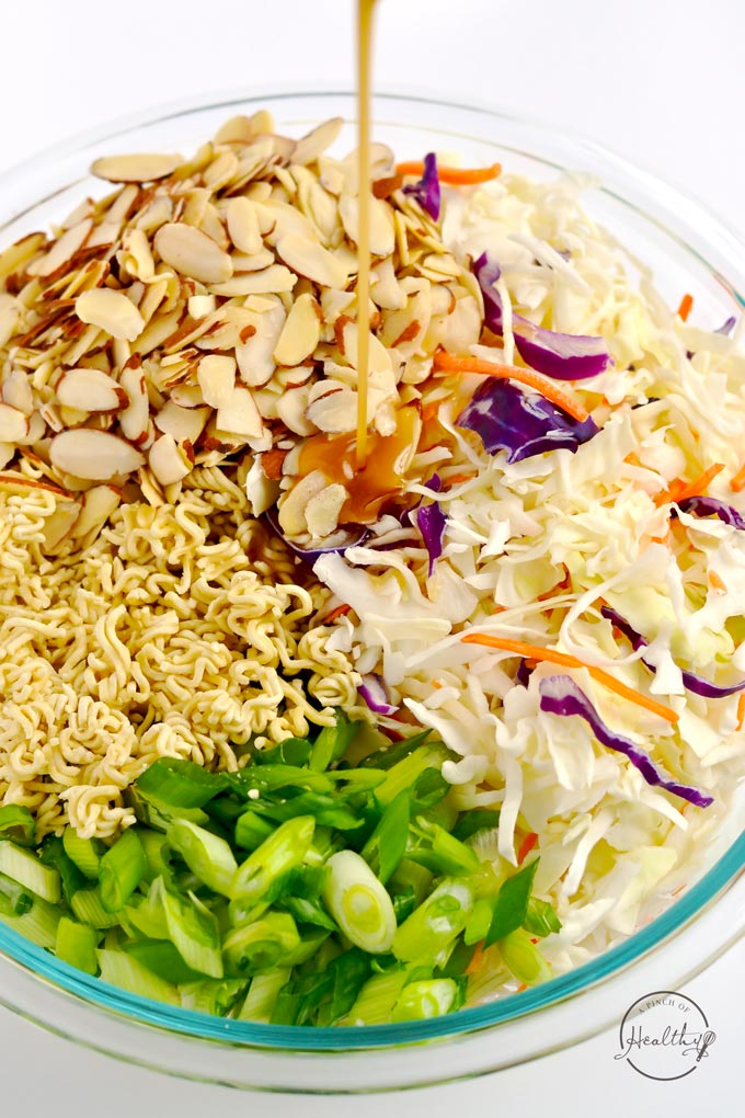pouring dressing on cabbage, almonds, green onion and ramen noodles in a clear bowl