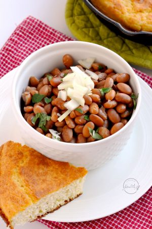 pinto beans in white bowl with diced onion and corn bread
