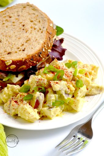 classic potato salad on a white plate with a sandwich