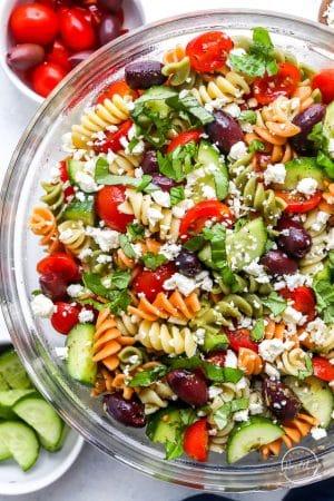 Closeup side shot tossed Greek Pasta Salad in glass bowl
