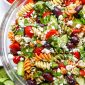 Closeup side shot tossed Greek Pasta Salad in glass bowl