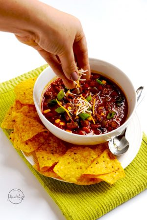 Taco soup is with hand sprinkling cheese on top