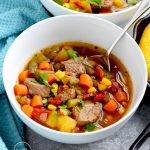 Closeup white bowl with Instant Pot vegetable beef soup and a spoon
