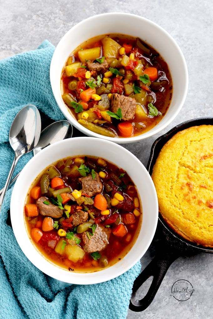 Instant Pot vegetable beef soup in two white bowls with skillet corn bread