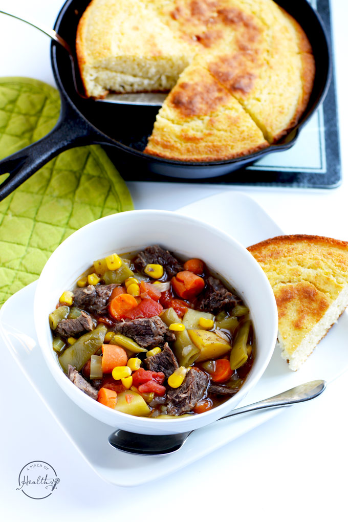 Instant pot vegetable beef soup in a white bowl with cornbread