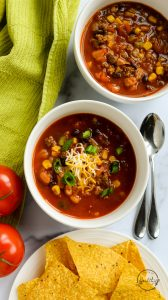 taco soup with cheese and green onion marble counter
