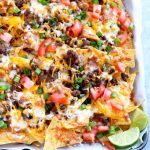 epic beef nachos supreme with lime slices
