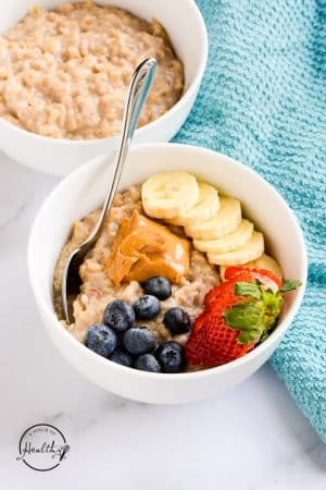White bowl with oatmeal topped with peanut butter and berries, with a blue towel on the side