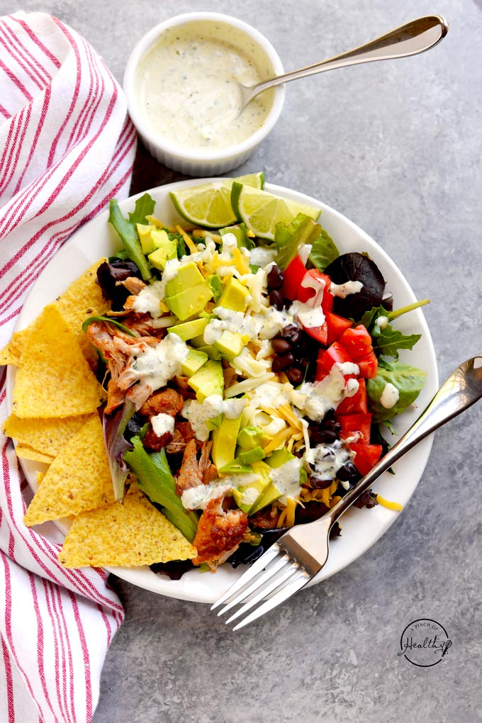 Chicken taco salad with avocado, black beans, tomatoes, cheese and creamy jalapeño ranch dressing
