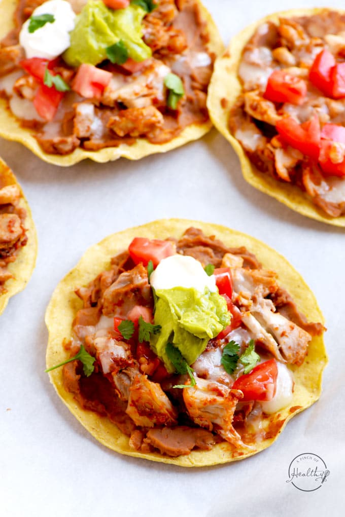 Chicken tostadas with refried beans, chicken, cheese, tomatoes, guacamole and sour cream