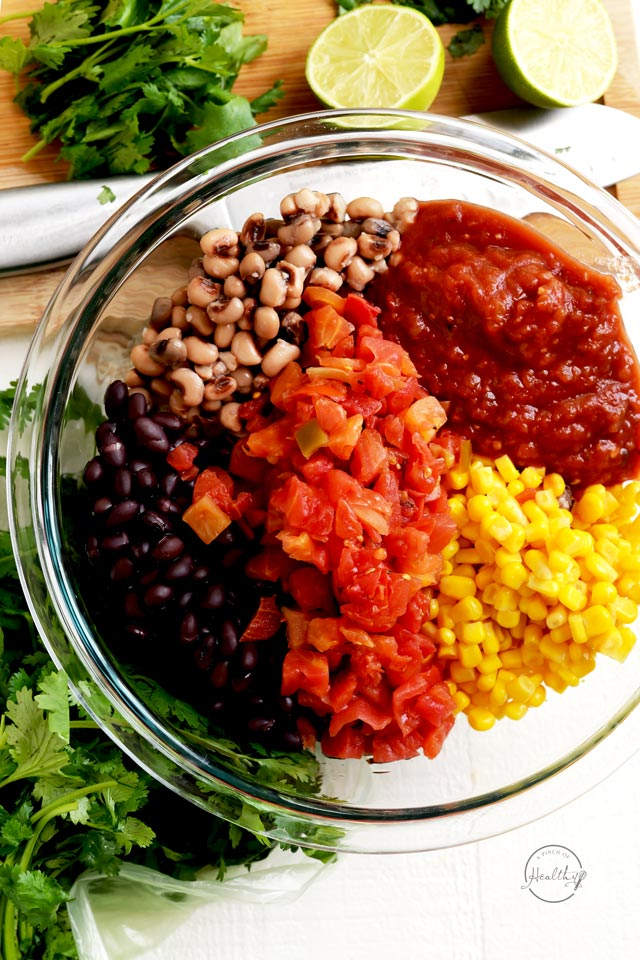 Making cowboy caviar piles of tomato, black beans, black eyed peas, corn and salsa