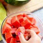 Hand grabbing a watermelon cube