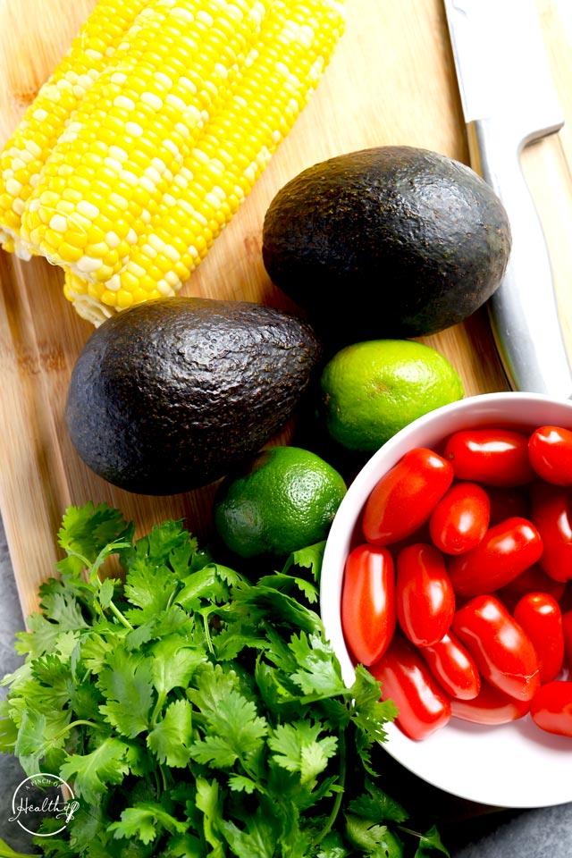 corn, avocado, limes, tomato and cilantro on cutting board
