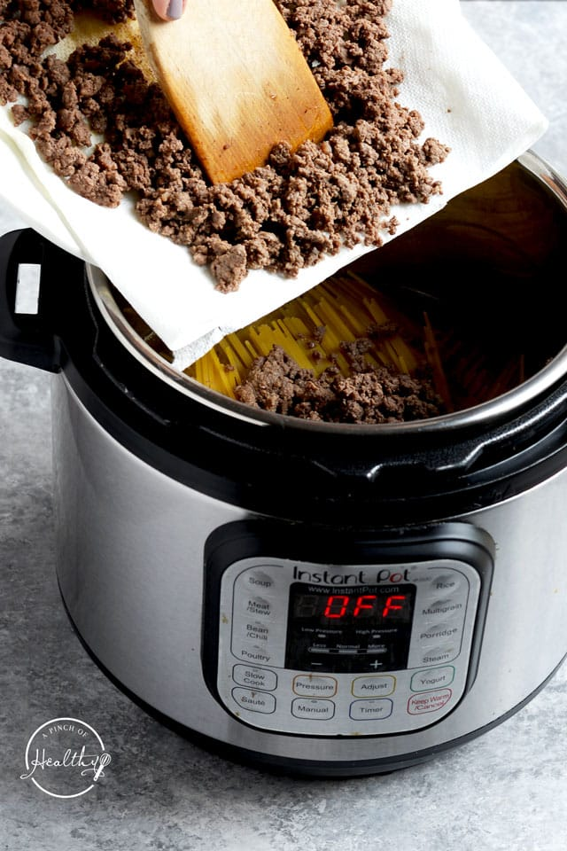 adding ground beef to Instant Pot on top of pasta